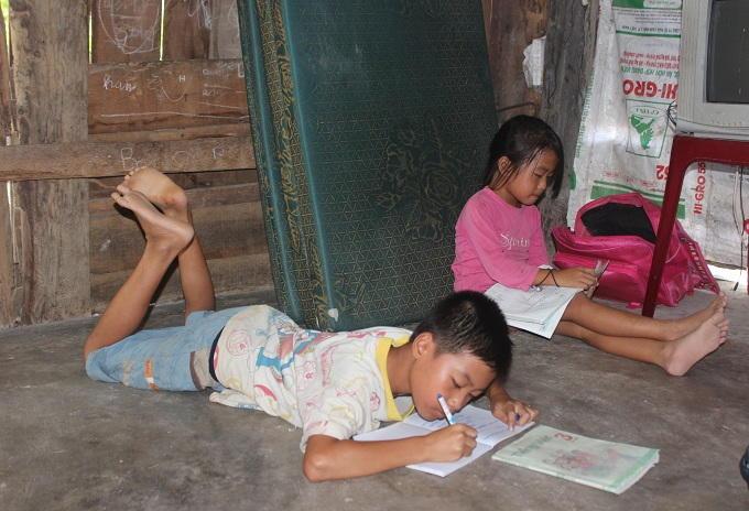 Vì gia đình quá nghèo, nên 2 con của anh Trương Ngọc Chung không có bàn học tập mà phải nằm, ngồi giữa căn nhà tạm để học bài.