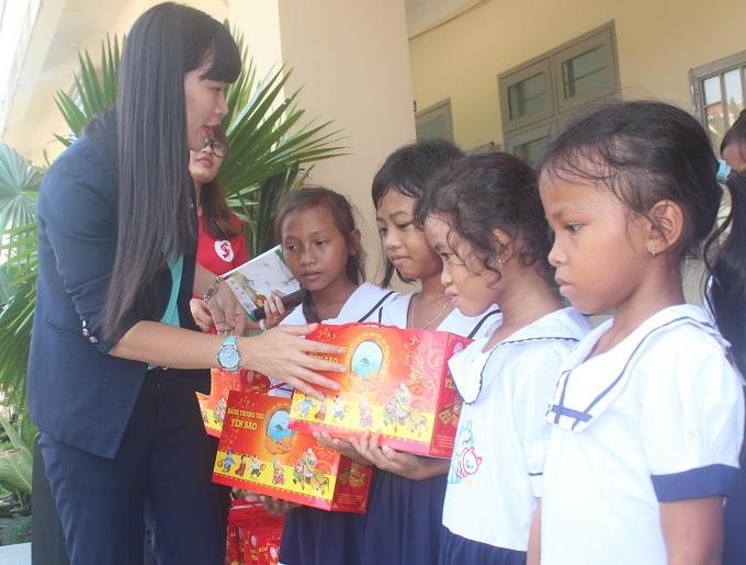 Đại diện Công ty Yến sào Khánh Hòa trao quà trung thu sớm cho các em học sinh.